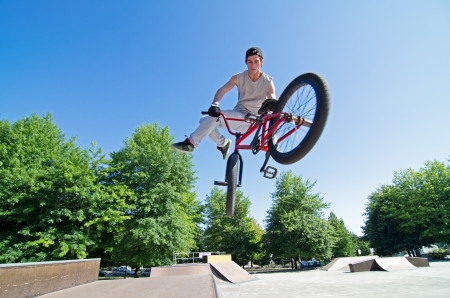 Bmx rider performing a tail whip at a quater pipe ramp on a skatepark.