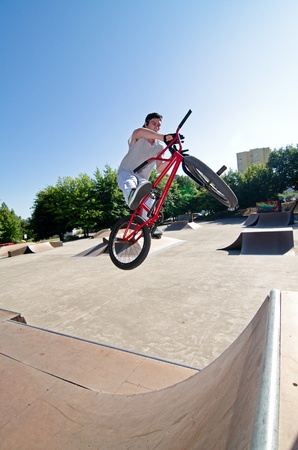 quater: Bmx rider performing a bar spin to a quater pipe ramp on a skatepark.