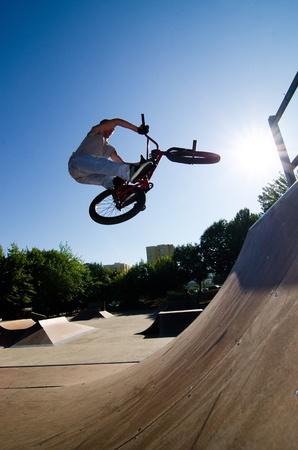 stunts: Bmx rider esegue una rotazione bar ad una rampa quater del tubo su una skatepark. Archivio Fotografico