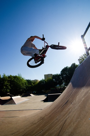 Bmx rider performing a bar spin to a quater pipe ramp on a skatepark.