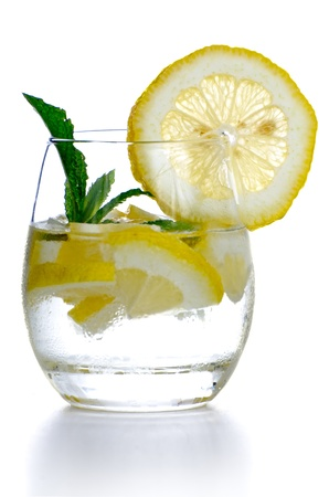 lemon water: Glass of fresh cool drink with lime fruits isolated on white background. Stock Photo
