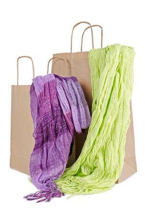 sciarpe: Shopping sacchetti di carta marrone con due sciarpe artigianali su sfondo bianco.