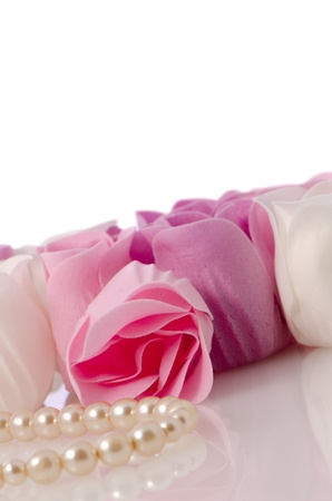Pink, purple and white beautiful luxury soap roses and a pearl necklace background. photo
