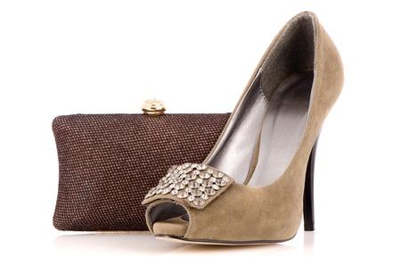 Female shoe and handbag on a white reflective background. photo