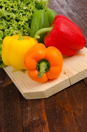 Yellow, red orange and green peppers, lettuce on wooden tray. photo
