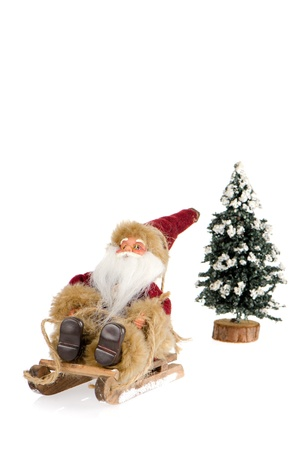 Miniature of Santa Claus on sleigh and a pine tree with snow, on white reflective background. photo