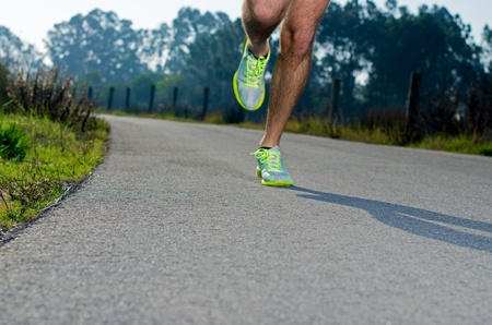 Running sport shoes outdoors in action on country road. Male shoes on young man training. Slight motion blur, focus on back running shoe. photo