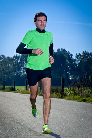 Male runner at sprinting speed training for marathon outdoors on crountry landscape. Stock Photo