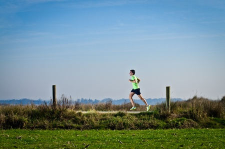 Male runner at sprinting speed training for marathon outdoors on crountry landscape. photo