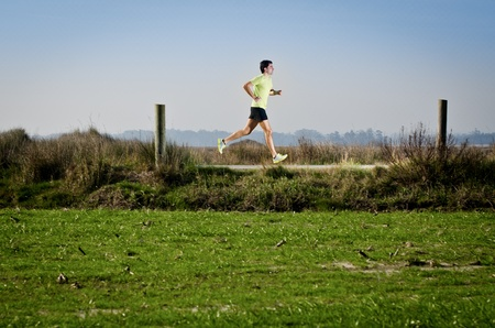 Male runner at sprinting speed training for marathon outdoors on country landscape. photo