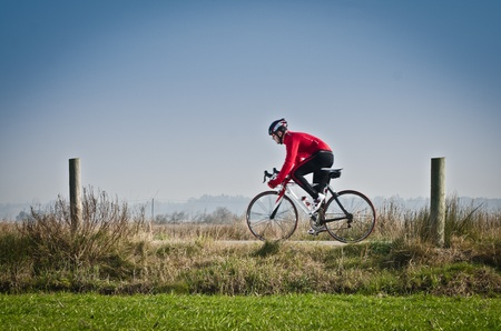 road bike: Man on road bike riding down open country road. Stock Photo