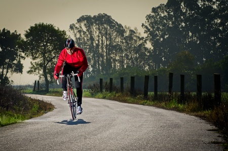 road cycling: Man on road bike riding down open country road. Stock Photo