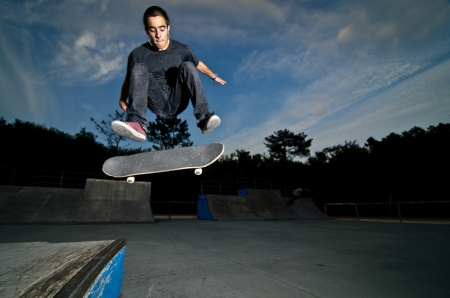 Skateboarder on a flip trick at the local skatepark. Stock Photo