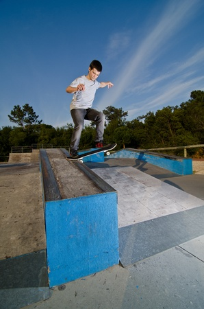 Skateboarder on a slide at the local skatepark. photo