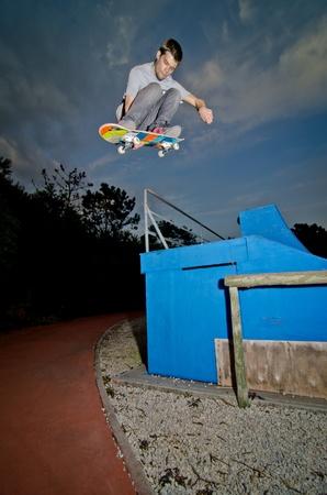 Skateboarder flying over a fap on sunset at the local skatepark. photo