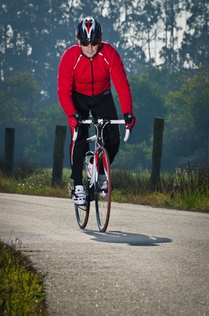 Man on road bike riding down open country road. Stock Photo - 12058104