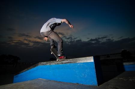 Skateboarder on a grind at the local skatepark.