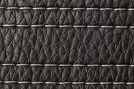 Closeup on a leather texture with a linear stitch.