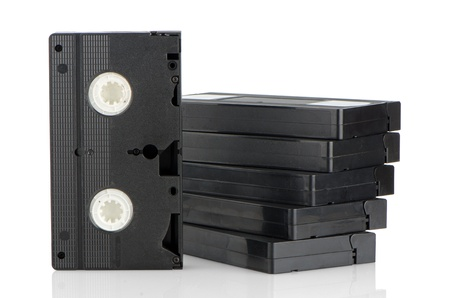 vhs videotape: Pile of videotapes on  white reflective background.