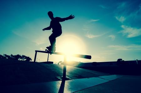 patín: Skateboarder silueta en una rutina en el skatepark local de