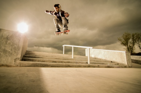 Skateboarder jumping over the stairs on a big ollie.