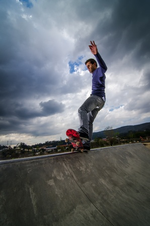 Skateboarder on a grind with dark clouds background at the local skatepark. photo