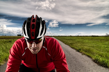Cyclist on road bike through a asphalt road and blue sky with clouds.