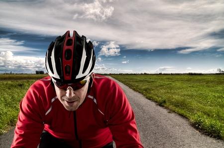 Radfahrer auf Rennrad durch eine asphaltierte Straße und blauen Himmel mit Wolken.