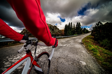 red competition: Cyclist on road bike through a asphalt road in the mountains and blue sky with clouds.