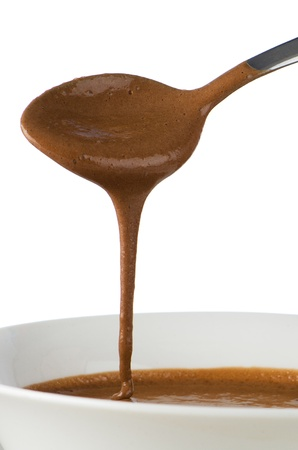 Chocolate dripping from spoon on white background. photo