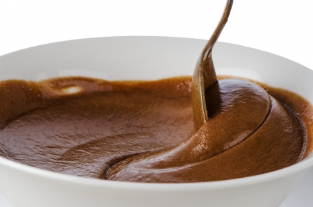 Chocolate mousse on a white mug with spoon on white background. photo