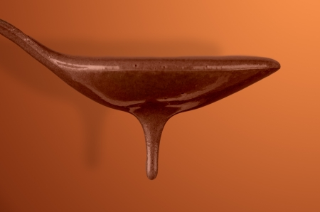 Chocolate dripping from spoon on gradient brown background. photo