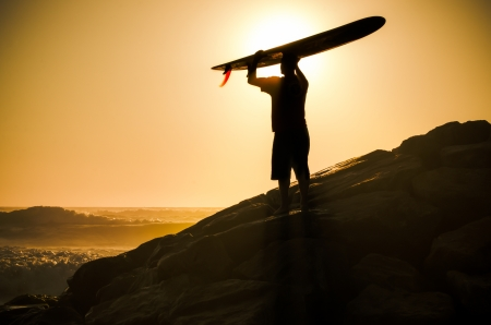 A longboarder watching the waves at sunset in Portugal. photo