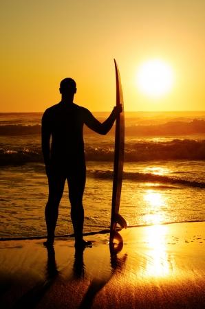 Ein Surfer die Wellen zu beobachten bei Sonnenuntergang in Portugal.