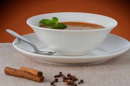 ou: Chocolate mousse ou a white mug with mint leaves.