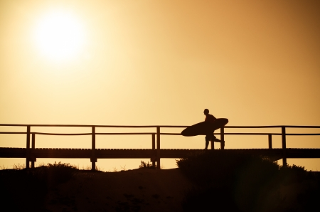 A surfer running to the beach at sunset in Portugal. photo