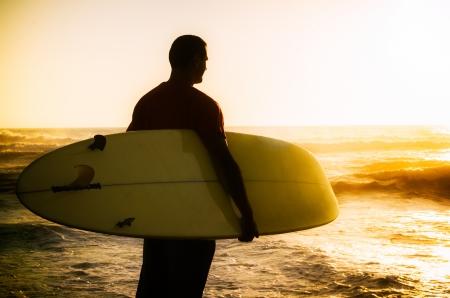 Ein Surfer beobachten die Wellen bei Sonnenuntergang in Portugal. Lizenzfreie Bilder