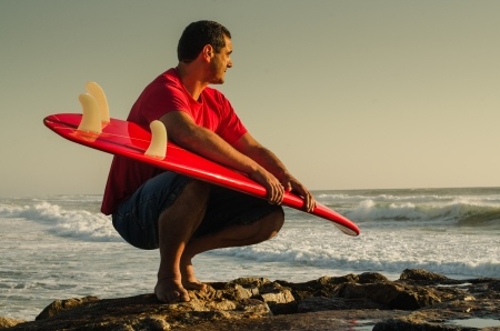 short wave: A surfer watching the waves sitting down with his arms around his surfboard.