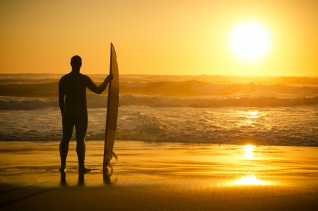 A surfer watching the waves at sunset in Portugal.