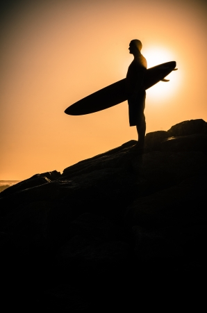 A surfer watching the waves at sunset in Portugal. photo