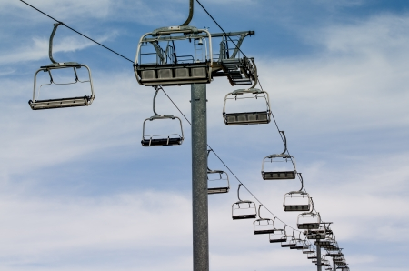 Idle lift chairs on cloudy blue sky. photo