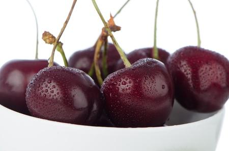 Cherry in white bowl on white reflective background. photo
