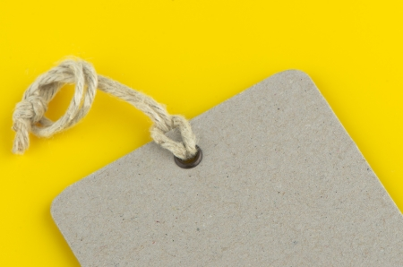 Closeup of blank product info label on yellow background. photo