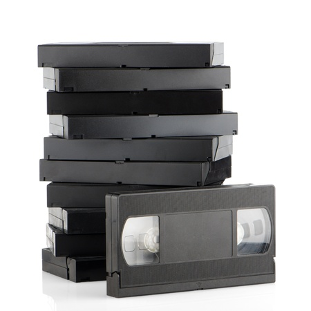 vcr: Pile of videotapes on  white reflective background.