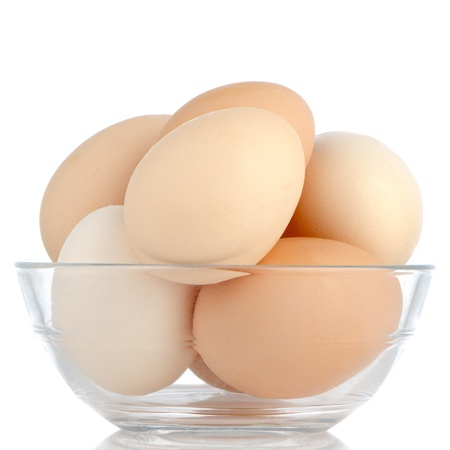 Brown eggs in transparent bowl isolated on white background. photo