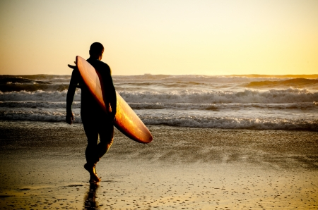 longboard: Surfer walking on the beach with the waves at sunset in Portugal.