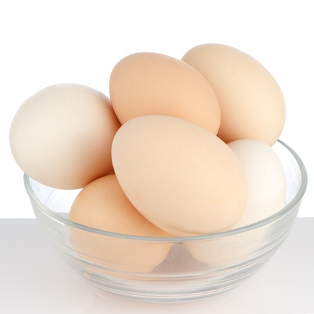 Brown eggs in transparent bowl on white background. Stock Photo - 14507806