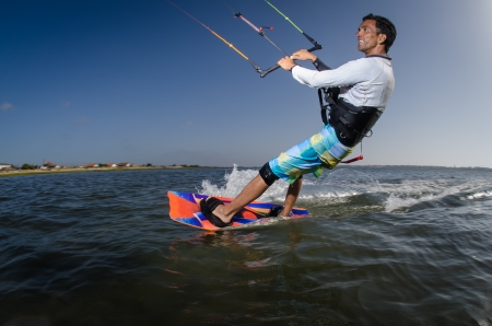 wet suit: Kiteboarder enjoy surfing on a sunny day.