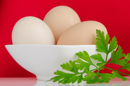 Eggs,Three eggs in the bowl on a red background. photo