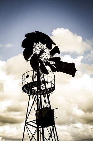 Old Farm Windmill for Pumping Water with Spinning Blades against cloudy sky. photo